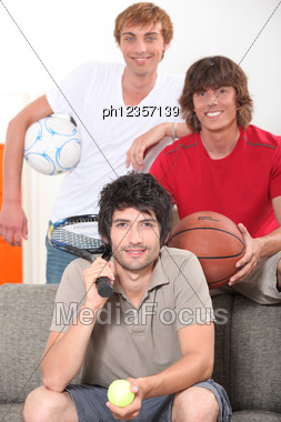 Three Male Friends With Various Sporting Equipment Stock Photo