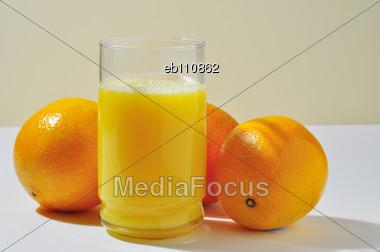 Three oranges and a glass of orange juice Stock Photo