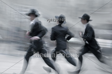 Three Orthodox Jewish Teenagers Running Down The Street Dressed In Traditional Suites And Hats Stock Photo