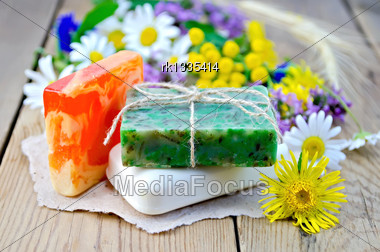 Three Pieces Of Homemade Soap On A Piece Of Paper, Chamomile Flowers, Tansy, Elecampane On The Background Of Wooden Boards Stock Photo