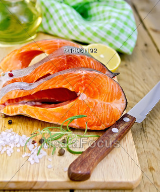Three Pieces Of Trout With Rosemary And Coarse Salt, Pepper, Knife, Vegetable Oil, Lemon, Napkin On The Wooden Board Stock Photo
