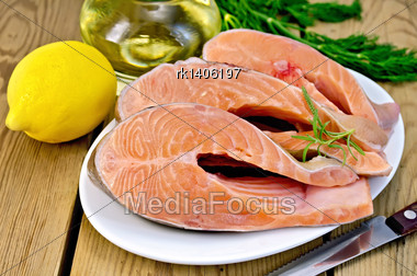Three Pieces Of Trout In White Plate With Rosemary, Lemon, Vegetable Oil, Dill On A Wooden Boards Background Stock Photo