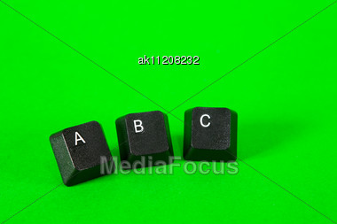 Three Plastic Keys With ABC Text Over Green Background Stock Photo