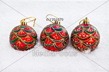 Three Red With Green, Silver And Gold Ornaments Christmas Ball On Snow Stock Photo