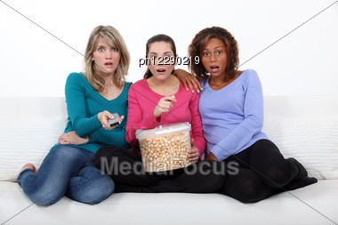 Three Scared Women Sat On Sofa Watching Movie Stock Photo