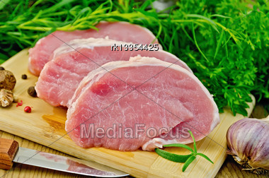 Three Slices Of Pork, Garlic, Nutmeg, Parsley, Tarragon, Rosemary And Dill, A Knife, Pepper Against A Wooden Board Stock Photo