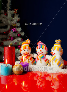 Three Snowmen And Burning Candles Over The Blue Background Stock Photo