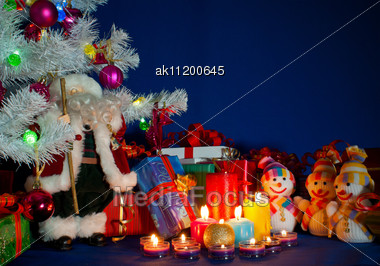 Three Snowmen In Front Of The Christmas Presents And Burning Candles Stock Photo