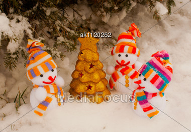 Three Snowmen With Golden Evergreen Tree Staying Outdoors Stock Photo