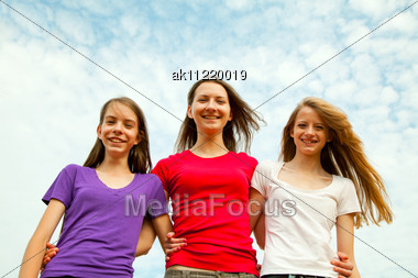 Three Teen Cheerful Girls Against Blue Sky Stock Photo