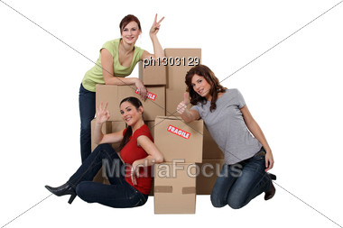 Three Women Gathered By Cardboard Boxes Stock Photo