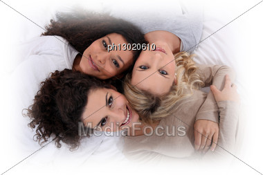 Three Women Laying Next To Each Other Stock Photo