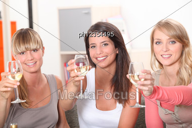 Three Women Toasting With Glass Of Wine Stock Photo