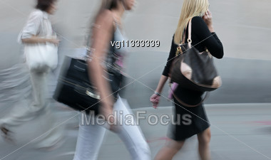 Three Women Walking On A City Street In Motion Blur, One Of Them Using On A Mobile Phone Stock Photo