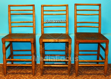 Three wooden chairs in front of azure color wall Stock Photo