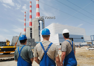 Three Workers Facing Power Plant Stock Photo