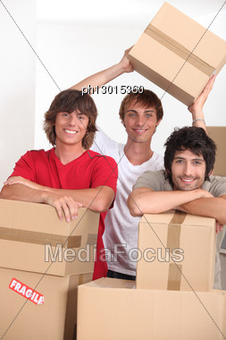 Three Young People In A Room Full Of Cardboard Boxes Stock Photo