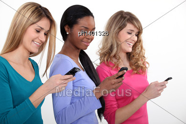 Three Young Women Using Their Mobile Telephones Stock Photo