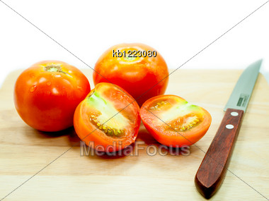 Tomato And Knife On Cutting Board Stock Photo