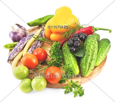 Tomatoes, Cucumbers, Sweet And Hot Peppers, Pea Pods, Three Pods Of Beans, Garlic, Parsley, Dill, Tarragon And Brush Aronia On A Wooden Circular Board Stock Photo