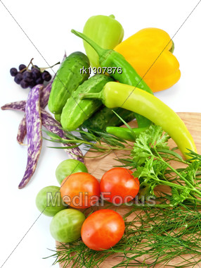 Tomatoes, Two Sharp Pepper, Parsley, Dill, Tarragon On A Wooden Board Round, Three Cucumbers, Two Sweet Peppers, Three Green Beans, Brush Chokeberry Isolated Stock Photo