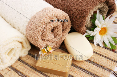 Towels And Olive Oil Soap With Aloe Vera, Flowers On Mat Background. Stock Photo