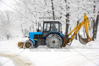 Tractor Of Dark Blue Color Deletes Snow In Park Stock Photo