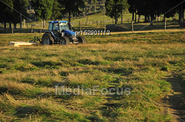 Tractor Mowing Pasture For Silage, West Coast, South Island, New Zealand Stock Photo