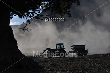 Tractor Spreading Lime With A Fertiliser Spreader, West Coast, New Zealand Stock Photo