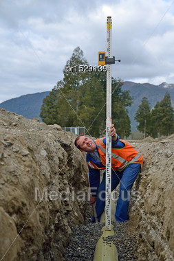 Tradesman Adjusts The Depth Of His Pipe In A New Stormwater Drain Stock Photo