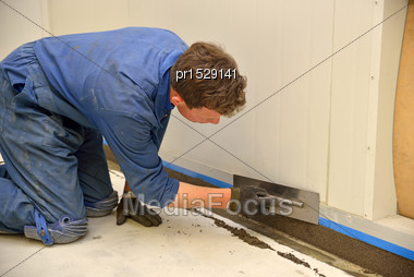 Tradesman Applying Epoxy Product To Coving Around The Floor Of An Industrial Building Stock Photo