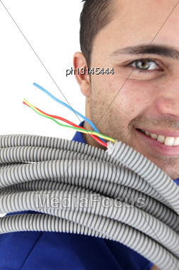 Tradesman Carrying Corrugated Tubing Stock Photo
