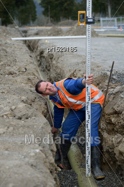 Tradesman Checks The Depth Of A New Stormwater Drain Stock Photo