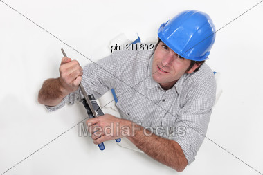 Tradesman Clasping A Chisel With A Pair Of Pliers Stock Photo