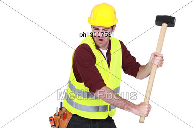 Tradesman Hitting An Object With A Mallet Stock Photo