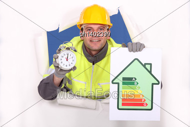 Tradesman Holding An Energy Efficiency Rating Chart And An Alarm Clock Stock Photo