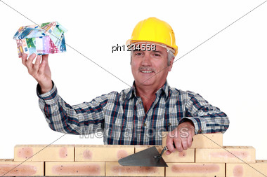 Tradesman Holding Up A House Model Make Out Of Money Stock Photo