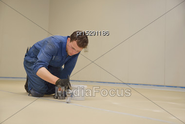 Tradesman Painting Edge Of Floor Line Before Epoxy Product Is Used In An Industrial Building Stock Photo