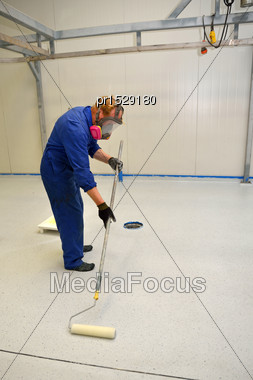 Tradesman Rolling Final Coat Of Clear Epoxy Product On The Floor Of An Industrial Building Stock Photo