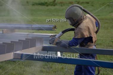 Tradesman Sandblasting Beams For Building Project Stock Photo