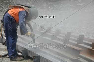 Tradesman Sandblasting I Beams For Building Project Stock Photo