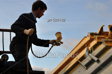Tradesman Spray Painting The Deck Of A Tip Truck Stock Photo