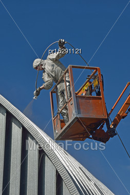 Tradesman Spray Painting The Roof Of An Industrial Building Stock Photo