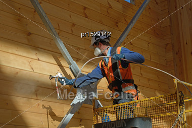 Tradesman Spray Painting Wall Wooden Industrial Building
