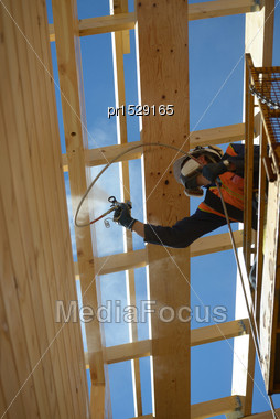 Tradesman Spray Painting The Wall Of A Wooden Industrial Building With Timber Preservative Stock Photo