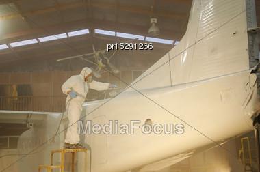 Tradesman Sprays The Fuselage On A Dornier 228 Aircraft Stock Photo