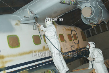 Tradesman Sprays The Fuselage On A Dornier 228 Aircraft Stock Photo