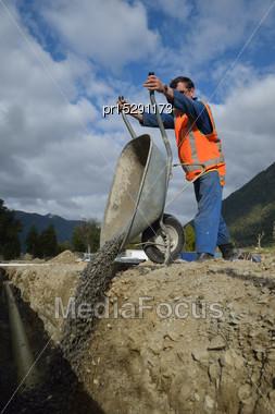 Tradesman Tips Gravel Into A New Stormwater Drain Stock Photo