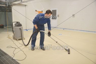 Tradesman Vacuums Floor Of An Industrial Building In Preparation For Painting Stock Photo