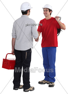 Tradesman Welcoming A New Recruit Stock Photo